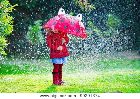 Little Girl In Red Jacket Playing In Autumn Rain