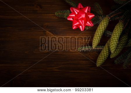 Spruce branch with cone and tied bow on wooden planks