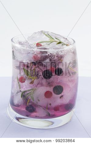 Natural Homemade Red Forest Fruit Coctail  With Ice, Lemon And Sliced Fruits In A Crooked Glass