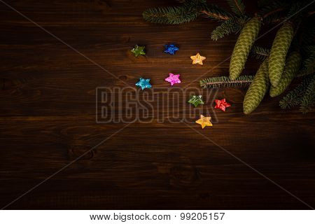 Spruce branch with cone and small stars on wooden planks
