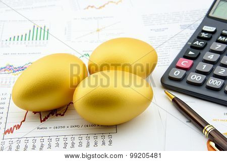 Three Golden Eggs With A Calculator On Business And Financial Reports.
