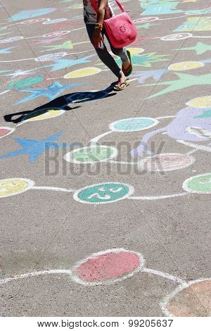 Child Jumping On The Childish Drawings On The Asphalt