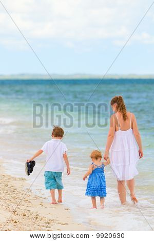Family Walking Along Tropical Beach