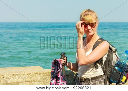 Young Woman With Backpack Hiking On Sea Coast