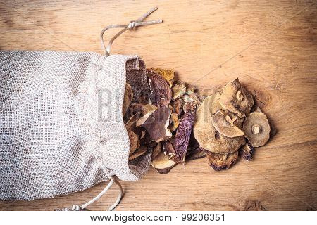 Dry Mushrooms In Sack On Wooden Table.