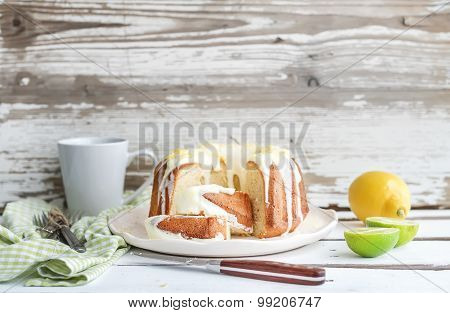 Moist lime and lemon bundt yoghurt cake, white rustic wooden  background.
