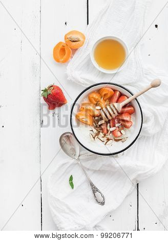 Healthy breakfast set. Rice cereal or porridge with fresh strawberry, apricots, almond and honey ove
