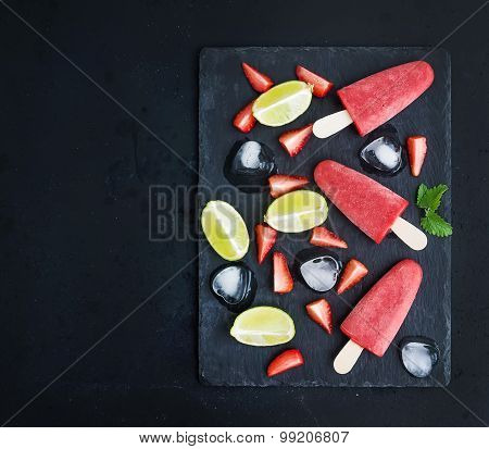 Strawberry and lime ice-creams or popsicles with fresg cut berries, citruses, ice cubes, melissa lea