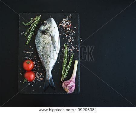 Fresh uncooked dorado or sea bream fish with vegetables, herbs and spices on black slate tray over d