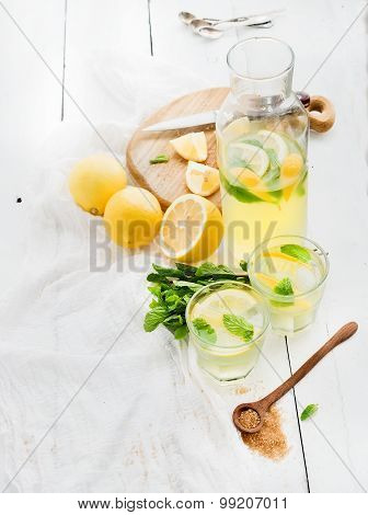 Fresh homemade lemonade with lemons and mint on white wooden background