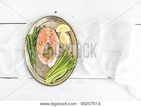 Raw salmon steak with asparagus, lemon, spices and rosemary on vintage silver tray over white wooden