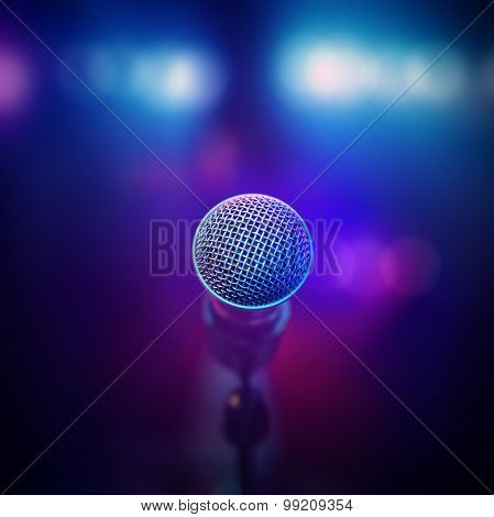 Musical microphone close-up from behind facing out of focus stage lights