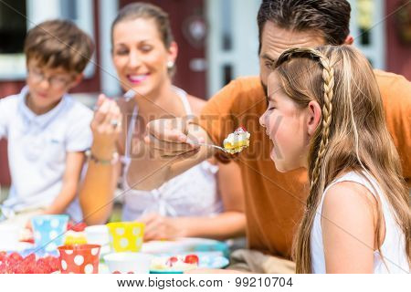 Family with cake in summer garden