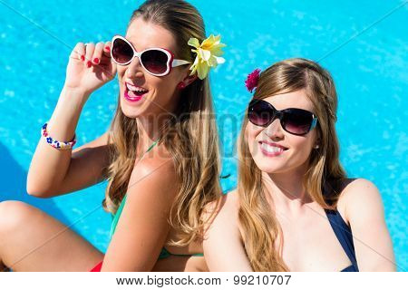 Girl friends tanning at swimming pool in the sun in front of the water leaning against each other