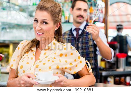 Woman customer in coffee bar drinking cup of cappuccino, in background the barista is preparing a beverage