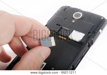 Human Hand Inserting Micro Sd Card Into Cell Phone (smartphone)