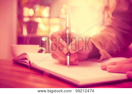 Man Hand Holding A Pen Writing On The Notebook.