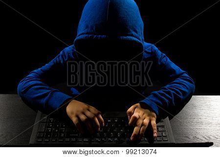 Faceless Hacker Using Computer