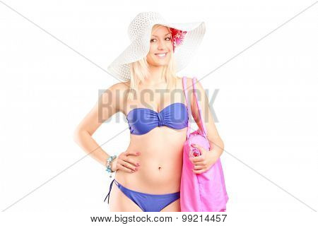 Young woman in bikini holding a pink bag isolated on white