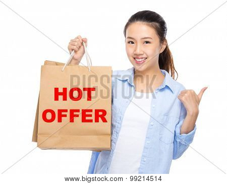 Woman with shopping bag and thumb up for showing hot offer
