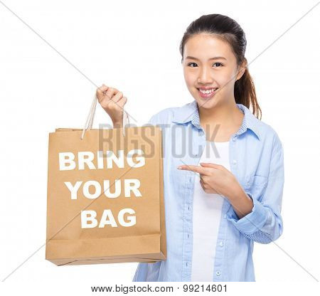Asian woman finger point to shopping bag and showing bring your bag