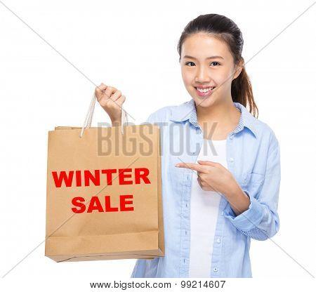 Asian woman finger point to shopping bag and showing winter sale