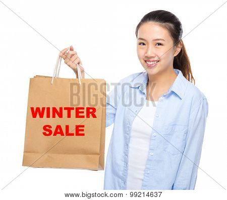 Young woman with shopping bag ans showing winter sale
