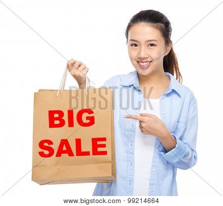 Asian woman finger point to shopping bag and showing big sale
