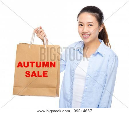 Young woman with shopping bag ans showing autumn sale