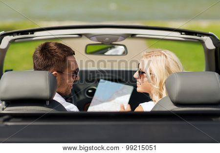 road trip, travel, leisure, couple and people concept - happy man and woman driving in cabriolet car with map