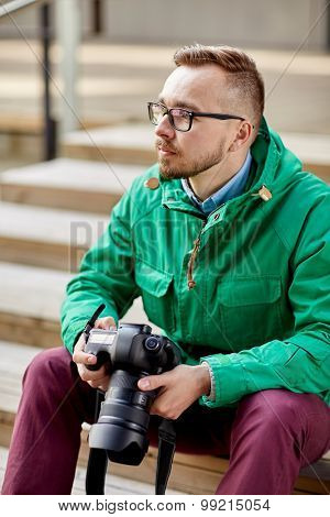 people, photography, technology, leisure and lifestyle - young hipster man holding digital camera with big lens and sitting on stairs in city