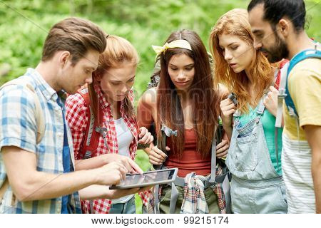 technology, travel, tourism, hike and people concept - group of friends walking with backpacks and tablet pc computer looking for location in woods