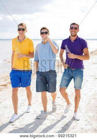 summer holidays, vacation, people and bachelor party concept - group of happy male friends drinking beer and walking along beach