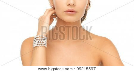beautiful woman wearing pearl earrings and bracelet