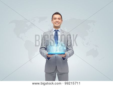 business, trade, people and technology concept - happy smiling businessman in suit holding tablet pc computer with hologram of shopping trolley over world map on gray background