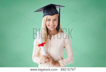 people, education, high school and graduation concept - happy student girl in bachelor cap with diploma over green chalk board background