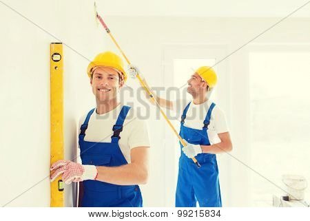building, teamwork and people concept - group of smiling builders in hardhats with tools indoors