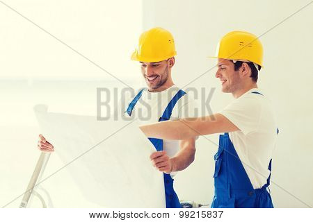 business, building, teamwork and people concept - group of smiling builders in hardhats with blueprint indoors
