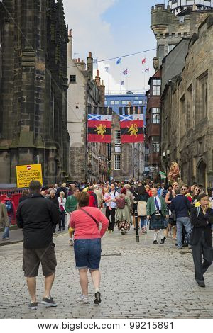 EDINBURGH, SCOTLAND - AUGUST 17, 2015:   Tourists walking in Edinburgh during the fringe festival the largest festival in the world.  Only the crowd and building in focus.