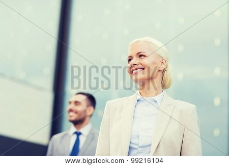 business, partnership, success and people concept - close up of smiling businessman and businesswoman standing over office building