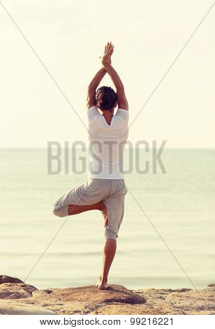 fitness, sport, people and lifestyle concept - young man making yoga exercises on beach from back