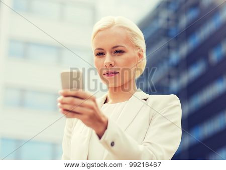 business, technology and people concept - serious businesswoman with smartphone over office building