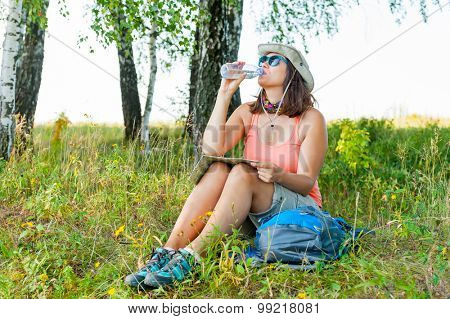 Young woman hiker drinks water in birch wood