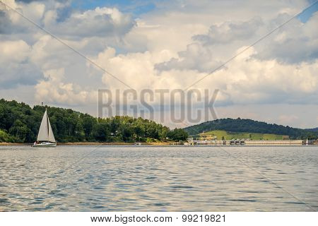 Sailboat on Solina lake and dam in Bieszczady mountains, Poland