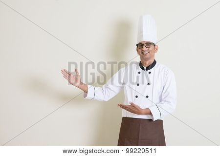 Portrait of handsome Indian male chef in uniform hands gesturing showing something and smiling, standing on plain background with shadow, copy space at side.