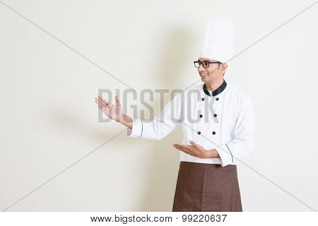 Portrait of handsome Indian male chef in uniform hands showing something and smiling, standing on plain background with shadow, copy space at side.