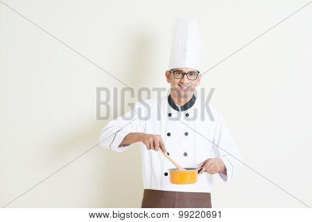 Portrait of handsome Indian male chef in uniform cooking food, standing on plain background with shadow, copy space on side.