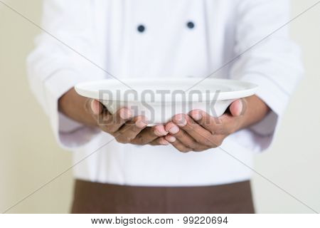 Black male chef in uniform presenting an empty dish