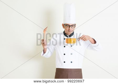 Portrait of handsome Indian male chef in uniform smelling the food aroma, standing on plain background with shadow, copy space on side.