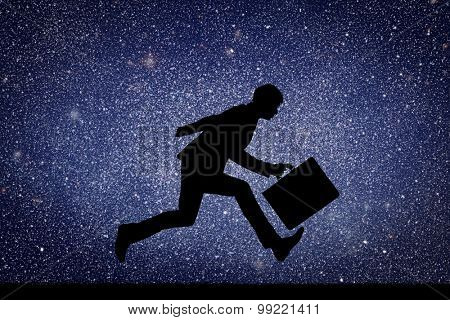 Businessman running with a briefcase against the background of starry sky